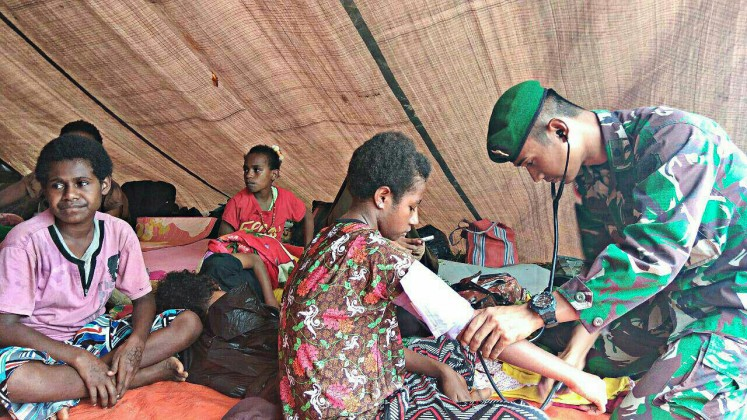 Challenging task: A member of the army provides health care to local residents in a village in Papua. Poor access to healthcare services in Papua's remote areas remains unresolved.