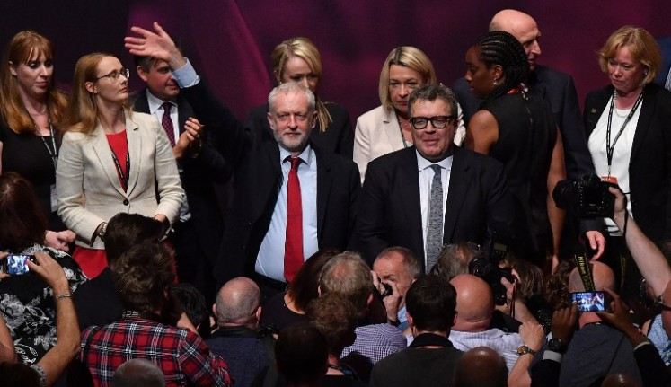 Britain's opposition Labour party Leader Jeremy Corbyn (left) waves as he stands with members of his shadow cabinet after Britain's opposition Labour party's Deputy Leader Tom Watson (right) delivered a speech on the third day of the Labour Party conference in Brighton, southern England, on Sept. 26, 2017.