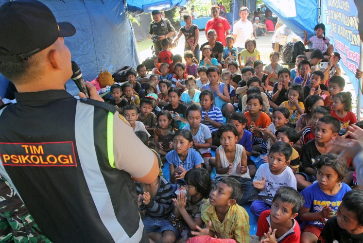 Listen up, kids: A policeman speaks with children at the Swecapura sports complex, which has become one of the centers for evacuees fleeing from the rumbling Mount Agung in Bali.