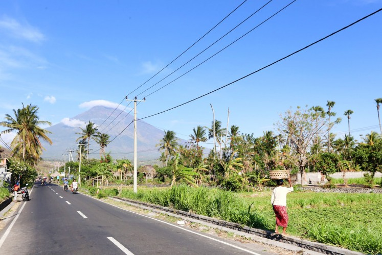 Deceptively calm: People go about their daily activities in the shadow of the rumbling Mount Agung in Bali.