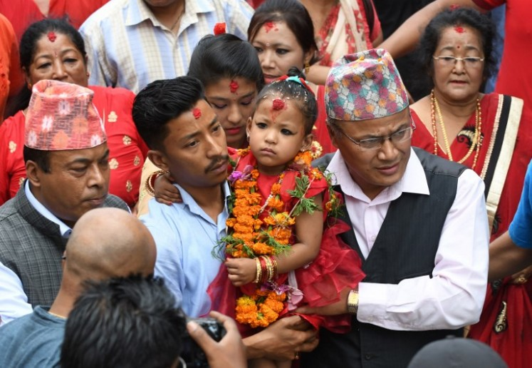 Trishna Shakya (center), 3, is carried by her father Bijaya Ratna Shakya (left) as she heads to Kumari House where she will live for the next few years as the new Kumari, and worshipped as a living goddess, in Kathmandu on Sept. 28, 2017.
