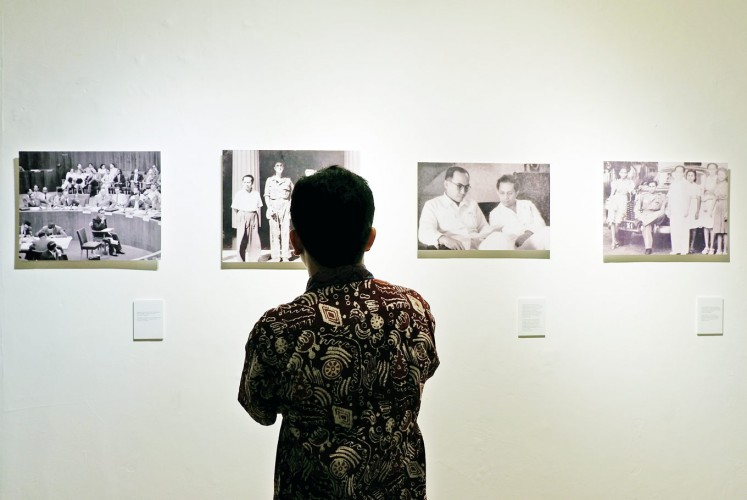 History revisited: A visitor enjoys photographs related to the history of the Banda Islands.
