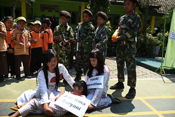 Fun learning: Students of elementary school SD 1 Dinoyo in Malang, East Java, on Friday act in a drama resembling the death of Ade Irma Suryani Nasution during the 1965 communist coup attempt.