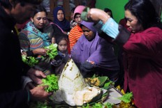 Female villagers cook tumpeng (rice cones) with side dishes of vegetables for the offering. JP/Magnus Hendratmo