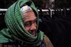 An elderly villager tries to keep warm. JP/Magnus Hendratmo
