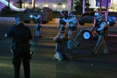 Police officers stop a man who drove down Tropicana Ave. near Las Vegas Boulevard and Tropicana Ave, which had been closed after a mass shooting at a country music festival that left at least 2 people dead nearby on October 2, 2017 in Las Vegas, Nevada. The man was released.  AFP/Getty Images/ Ethan Miller