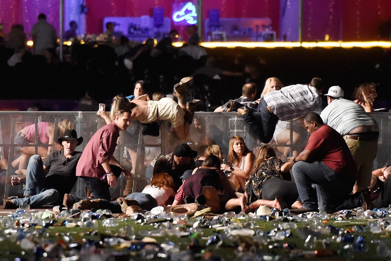 People scramble for shelter at the Route 91 Harvest country music festival after apparent gun fire was heard on October 1, 2017 in Las Vegas, Nevada. A gunman has opened fire on a music festival in Las Vegas, leaving at least 20 people dead and more than 100 injured. Police have confirmed that one suspect has been shot. The investigation is ongoing. AFP/Getty Images/David Becker