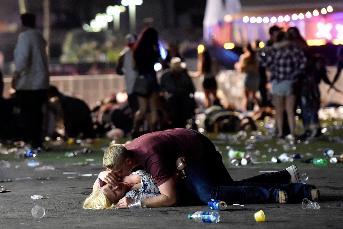 A man lays on top of a woman as others flee the Route 91 Harvest country music festival grounds after a active shooter was reported on October 1, 2017 in Las Vegas, Nevada. A gunman has opened fire on a music festival in Las Vegas, leaving at least 2 people dead. Police have confirmed that one suspect has been shot. The investigation is ongoing. AFP/Getty Images/David Becker