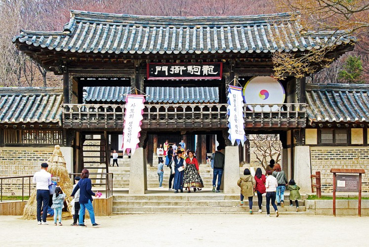 Walk into the past: A couple in traditional Korean outfits walk through an ancient entrance gate.