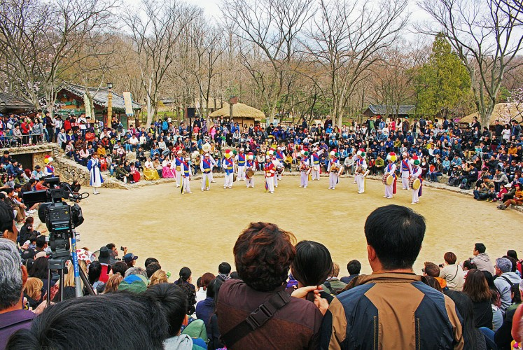 The show begins: Visitors flock to a small amphitheater to enjoy a farmer's dance.