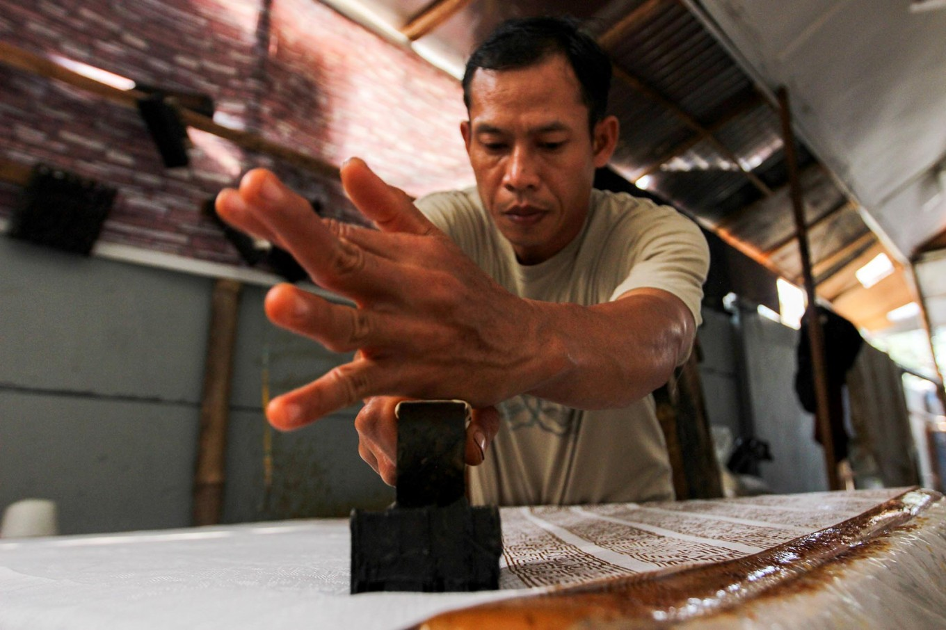 Consistency: A batik artisan carefully uses a copper stamp to print a batik motif. JP/Ibrahim Irsyad