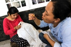 Manual work: Two batik artisans apply wax to the hand-drawn motifs.  JP/Ibrahim Irsyad