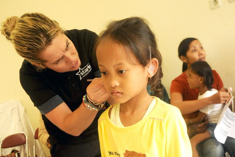 Incoming sounds: A girl stands still as a volunteer attaches the hearing aid.