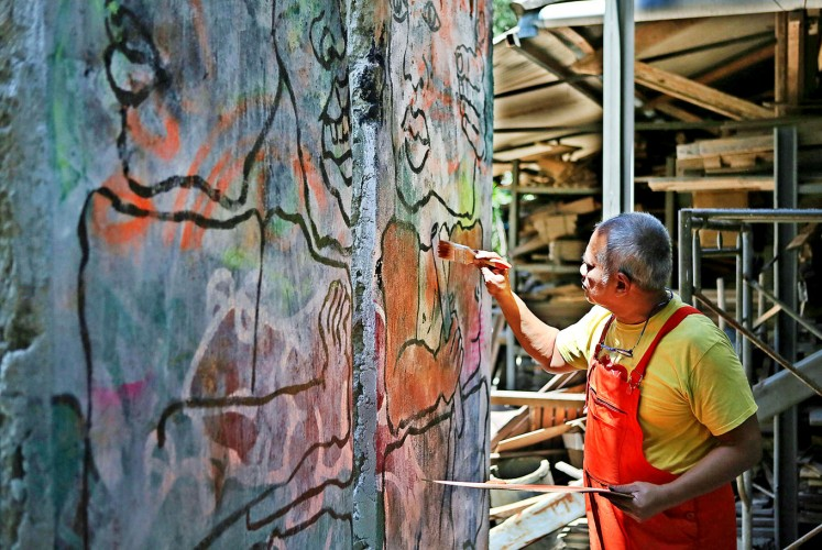 In progress: Artist Teguh Onsterik paints on a segment on the historic Berlin Wall at his workshop in Depok, West Java, on Aug. 2.