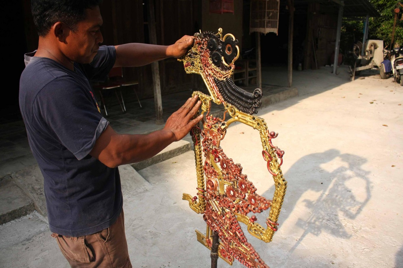 Agung holds a puppet made of used parts to be Sun dried. JP/Maksum Nur Fauzan