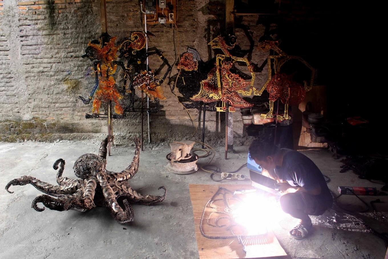 Agung welds a Gunungan (shadow puppet conical) from used parts. JP/Maksum Nur Fauzan
