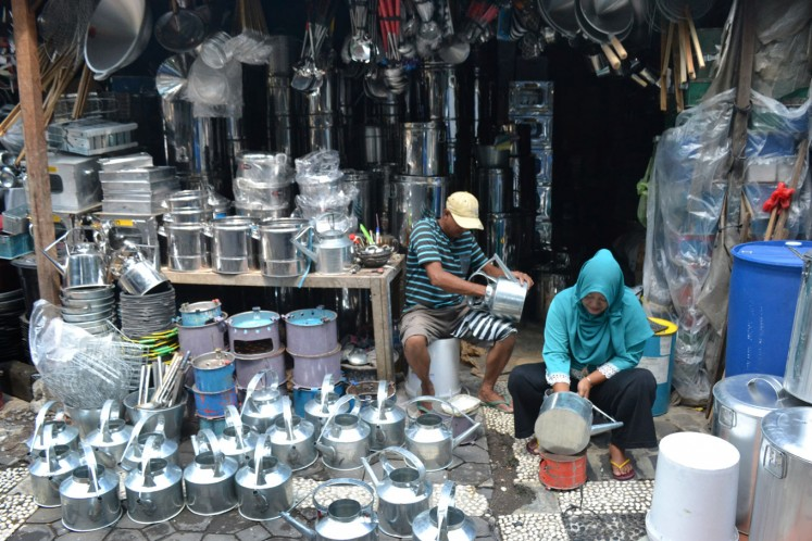 Vendors ready upcycled gas jugs in their stall at Kabangan Market.