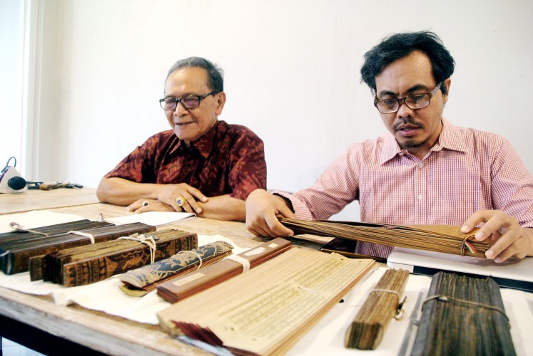 Experts: Ida I. Dewa Gde Catra (left) and Sugi Lanus expound the narrative on Mt. Agung written in ancient lontar (palm-leaf manuscripts).