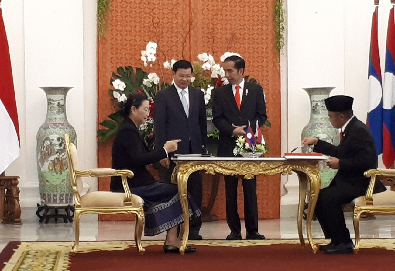 "Laos Education and Sports Minister Sengdeuane Lachanthaboun (left) and Culture and Education Minister Muhadjir Effendy sign a memorandum of understanding (MoU) on education cooperation, witnessed by Laos Prime Minister hongloun Sisoulith (second left) and President Joko ""Jokowi"" Widodo, at Bogor Palace in West Java on Oct. 12. Image: Anton Hermansyah 