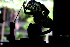 Action: A silhouette of a young puppet master performing a play. JP/ Maksum Nur Fauzan