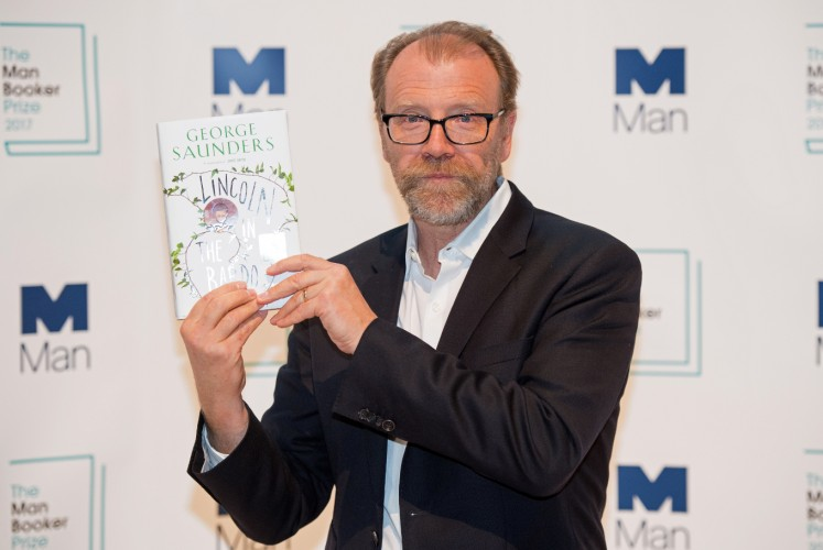 US author George Saunders poses with his book 'Lincoln in the Bardo' during a photocall at the Royal Festival Hall in London on October 16, 2017, ahead of tomorrow's announcement of the winner of the 2017 Man Booker Prize for Fiction.