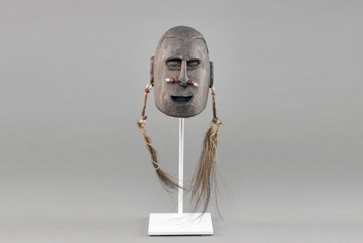 Tribal life: The wooden head statue symbolizes the Asmat people's old head hunting tradition.