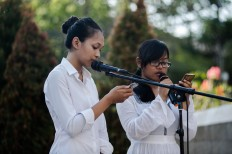 Wina (left) and Dinda (right) read a poem titled Surat Rindu Kami (Our Longing Letters) dedicated to their parents, who were killed in the bomb blasts. JP/Anggara Mahendra