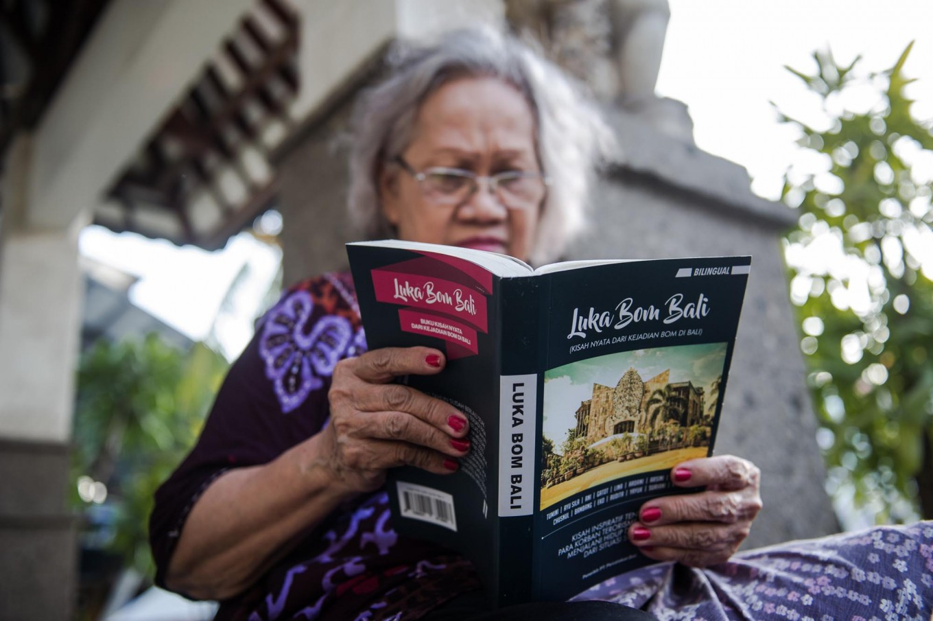 A woman reads Luka Bom Bali, which was released by the Isana Dewata Foundation on Oct. 12, 2017. The book was co-written by Ni Komang Erviani and Anak Agung Lea and tells the stories of 15 victims of the 2002 and 2005 Bali bombings. JP/Anggara Mahendra