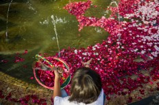 A young girl throws red rose petals into a pond in the middle of the monument. JP/Anggara Mahendra