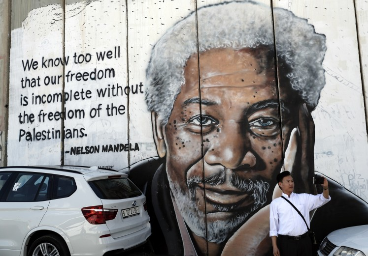 A man takes a selfie in front of a new piece of graffiti depicting US actor Morgan Freeman who played the role of former African president Nelson Mandela in the film 'Invictus'.