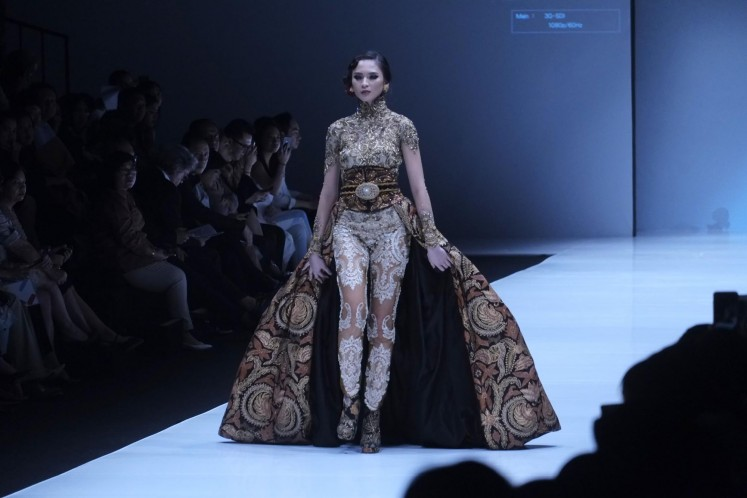 A  model struts down the catwalk wearing an Anne Avantie design at the opening show of Jakarta Fashion Week 2018.