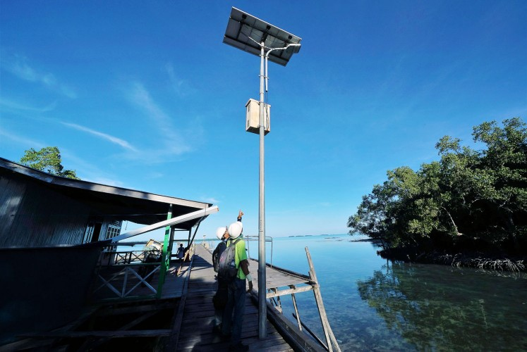 Green energy: Two workers check a street lamp that uses solar power on Teluk Harapan.