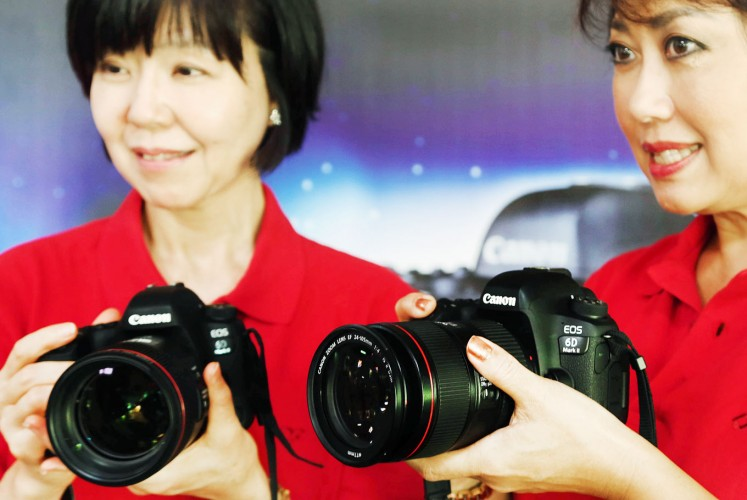 Introduction: Canon Singapore President and Chief Executive Officer Noriko Gunji (left) and Merry Harun, the Canon division director of PT Datascrip, the Indonesian sole distributor of Canon cameras, test the new camera.