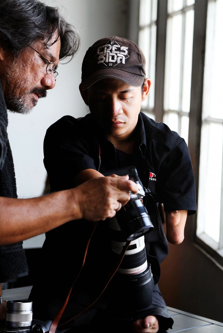 Watch and learn: Photographer Darwis Triadi (left) shares some snaps with Dzoel.