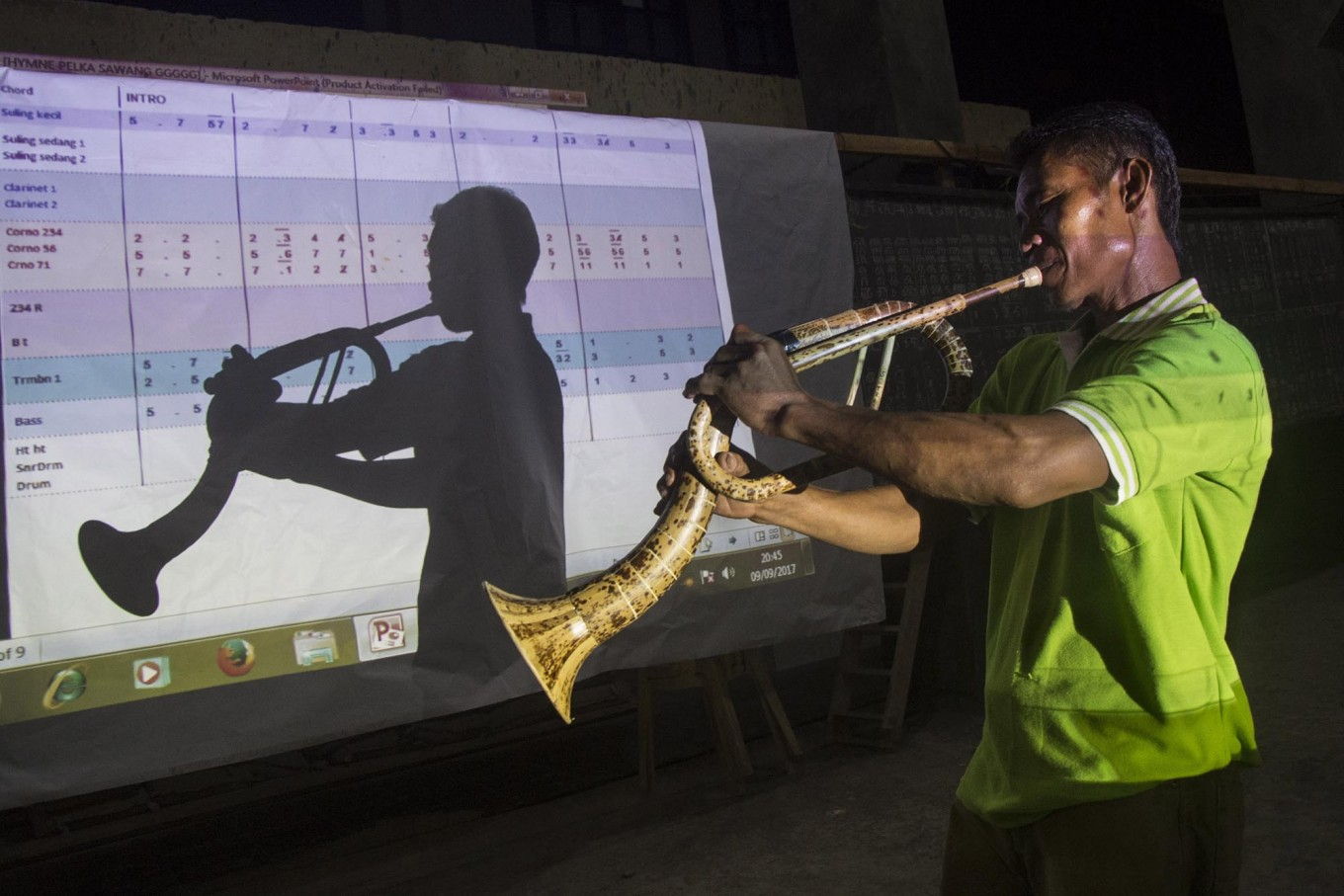 Perfect reflection: A trumpet player poses in front of a projector screen. JP/ Tarko Sudiarno
