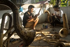 From scratch: Agustinus Sasundu (right) and his employee manually make bamboo instruments at his house. JP/ Tarko  Sudiarno