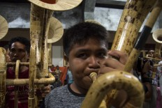 Whole-hearted: A boy blows into his tuba. Agustinus Sasundu's bamboo music troupe consists of musicians of all ages. JP/ Tarko Sudiarno