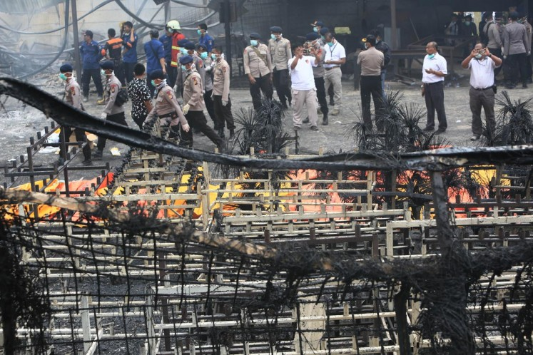 Officers evacuate victims of the fireworks factory blaze in Kosambi, Tangerang on Thursday.