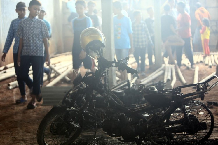 Residents look at the burnt motorcycle in the vicinity of the decimated fireworks factory in Kosambi, Tangerang on Thursday.
