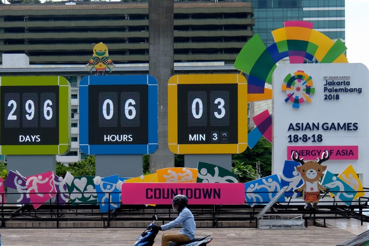 Bptj Prepares  Buses For Extension Of Odd Even Policy A Motorcyclist Rides Past The Asian Games