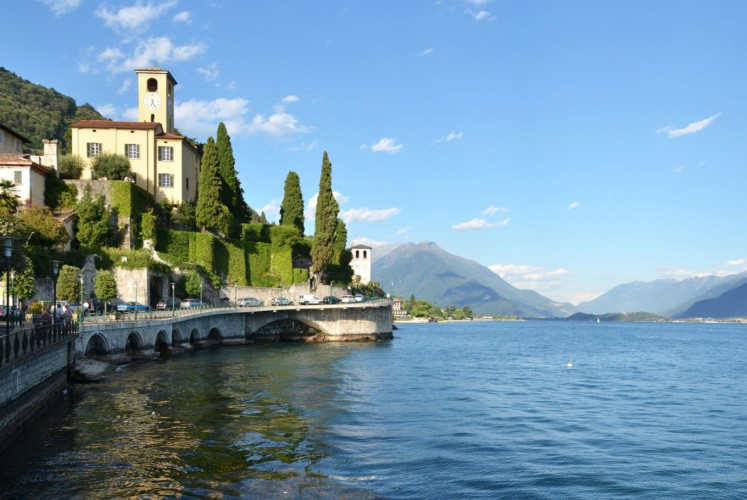 Lake Como is a town surrounded by sparkling blue calm water.