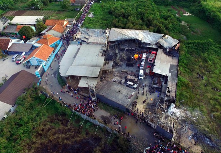 Residents are seen gathering outside the damaged fireworks factory in Kosambi, Tangerang on Thursday. The inferno killed 47 people and injured 46 others.