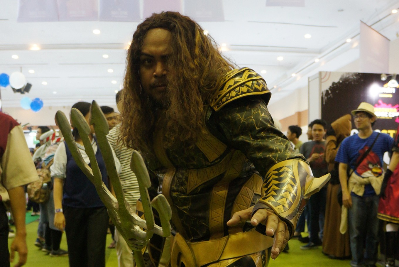 A cosplayer is dressed as Aquaman.