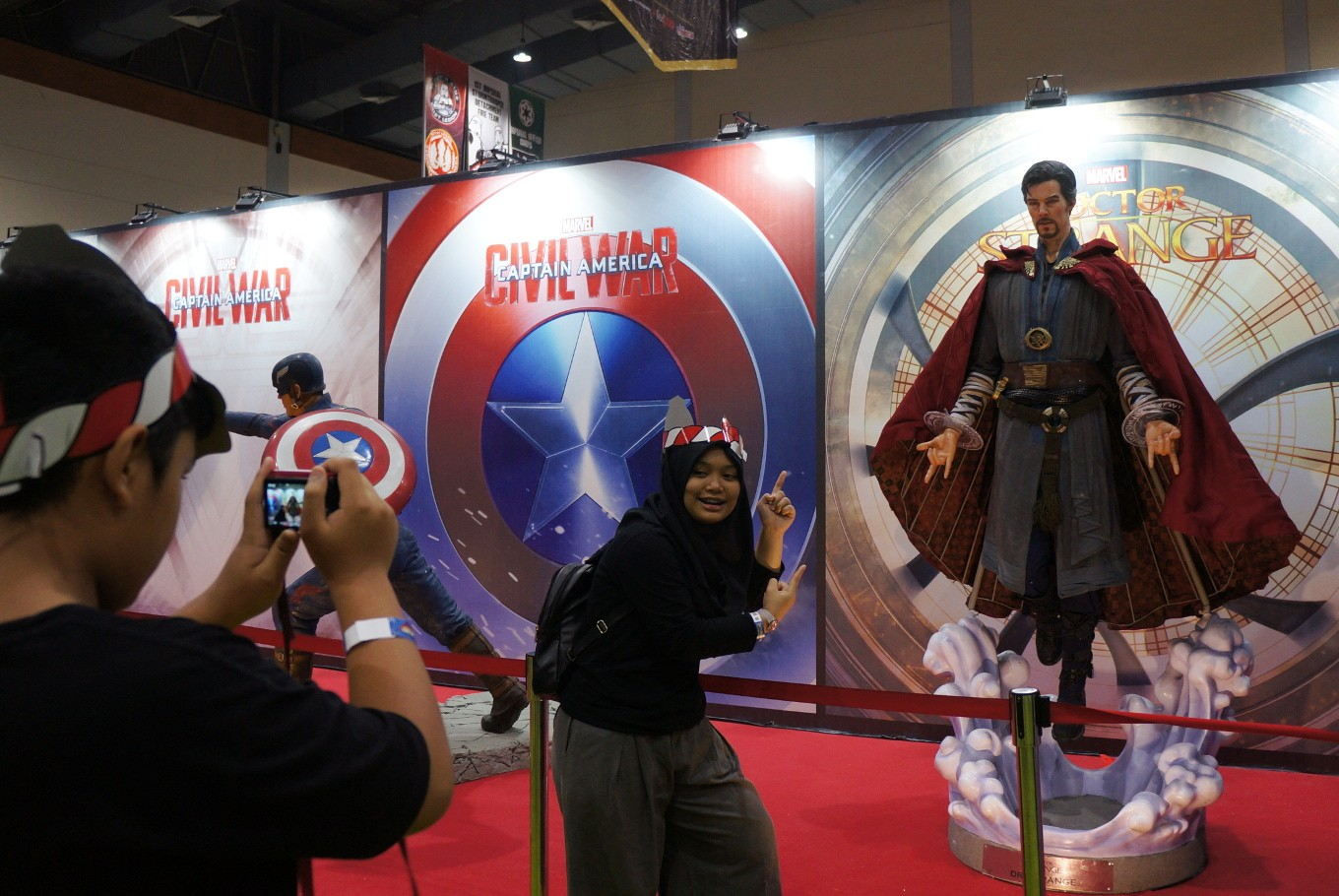 A visitor takes a photo next to a life-size sculpture of Marvel Cinematic Universe's Doctor Strange (Benedict Cumberbatch).
