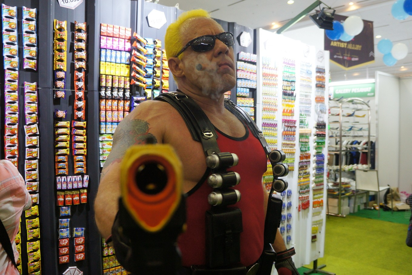 A cosplayer pulls out his gun while performing as 'Duke Nukem' from the video game series of the same name.