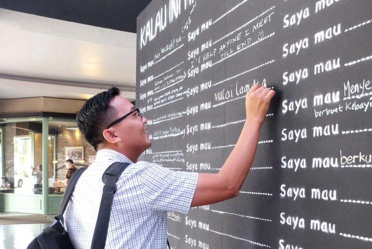 Public bucket list: A man writes on Rachel House's Living Wall during a recent campaign at the Cilandak Town Square mall in South Jakarta. On the wall, visitors can write down the things they would want to do if they knew they were living their final days.
