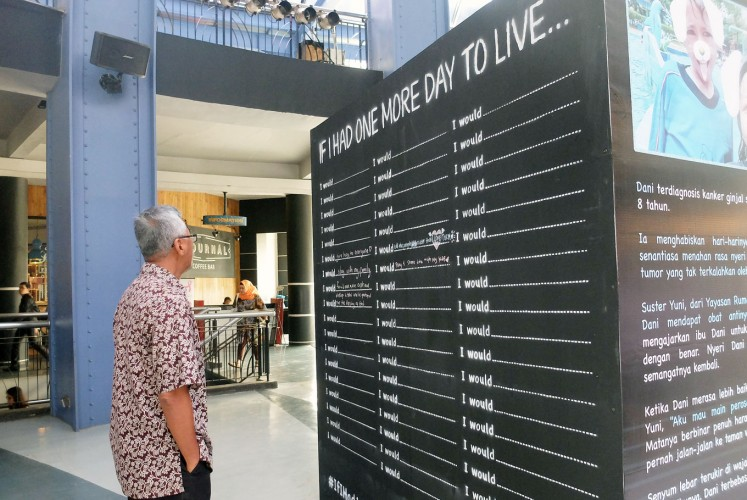 Reflection: A visitor reads bucket list items written on Rachel House's Living Wall.