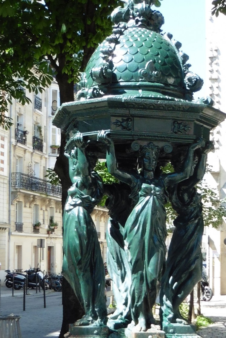 In the center of the square is a drinking-water fountain, one of more than a hundred to be erected in Paris after 1870.