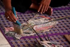 A museum official brushes a Dupara puppet at the museum. JP/Maksum Nur Fauzan