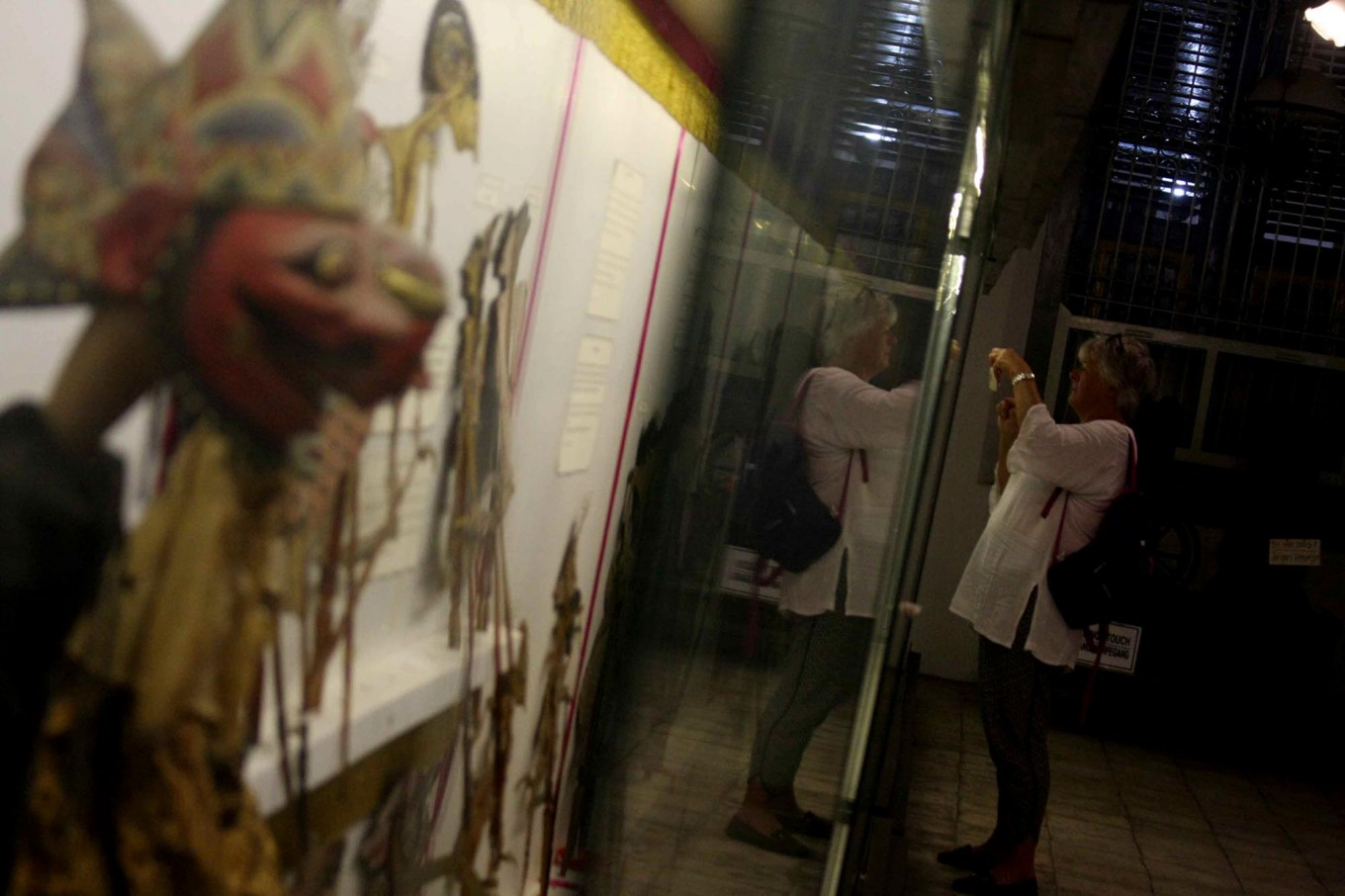A tourist takes a photo of the puppet collection at the Radya Pustaka Museum. JP/Maksum Nur Fauzan